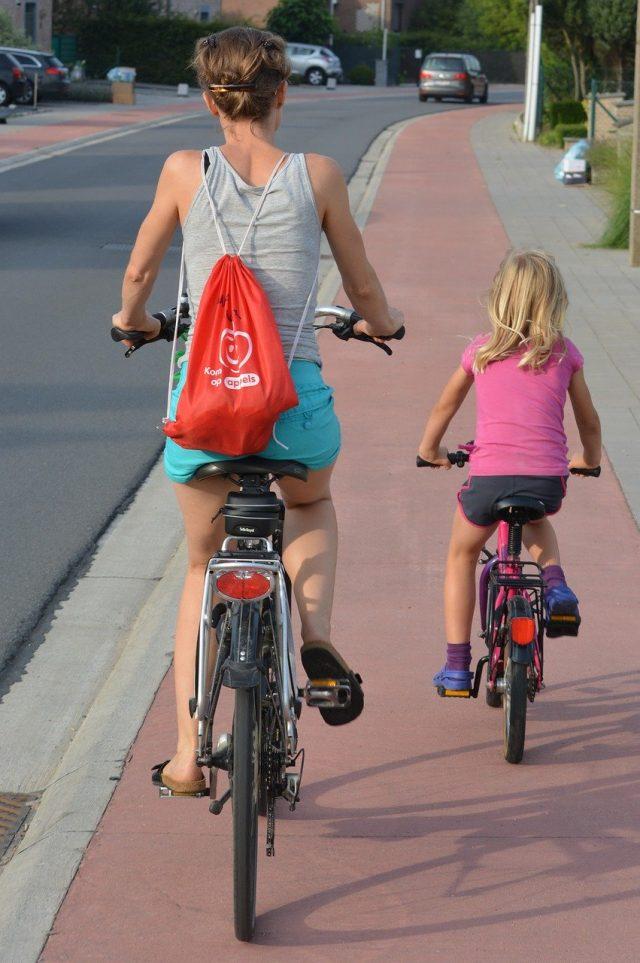Femme et sa fille en train de faire du vélo sur une piste cyclable