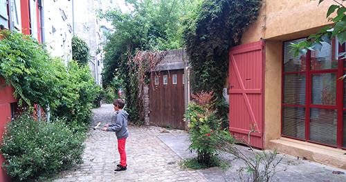 Enfant qui joue dans une rue où la nature est très présente